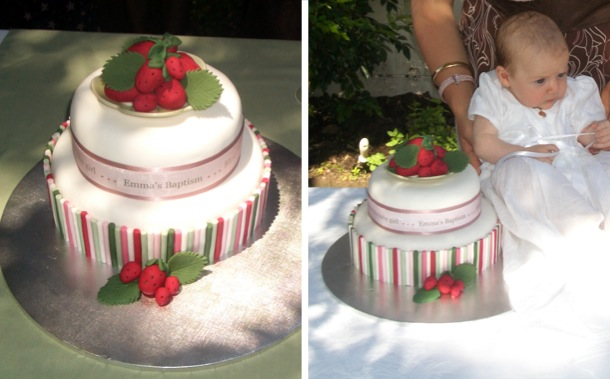 White royal icing cake with red, pink and green batons and loads of luscious strawberries