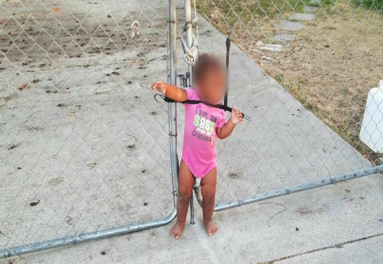 Toddler found strapped to fence