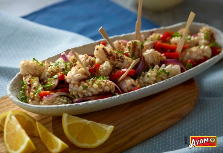 long oval platter filled with bbq marinated calamari, little bamboo toothpicks with wedges of lemon alongside the platter