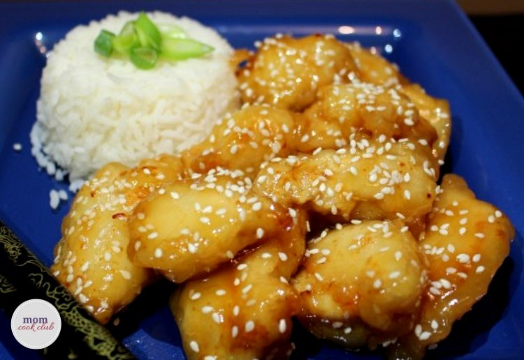 Delicous golden brown Sticky Honey Sesame Chicken sprinkled with sesame seeds and served with white rice on a blue plate