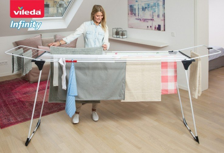 Woman hanging laundry onto the Vileda 27m Infinity Airer