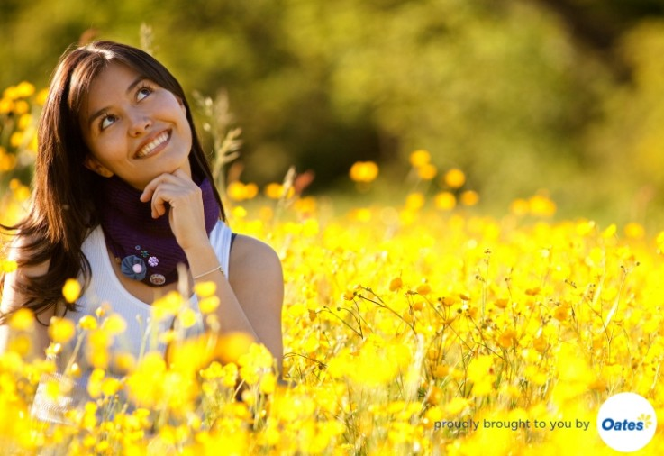 Beautiful woman in field of fresh yellow flowers looking up with her finger on her chin