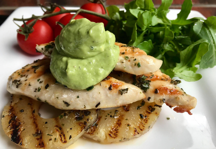 Grilled chicken with herbs, avocado dressing, ripe tomatoes and fresh greens