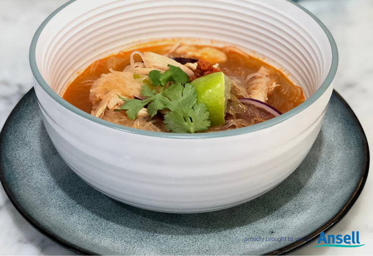 White Soup Bowl containing Tangy Chicken Soup which has a red curry stock base, vermicelli noodles, chicken, red onion, spring onions and coriander